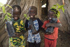 TFF three kids holding tree seeds